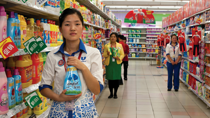 Promotion girls offer samples of  products and allow customers to taste, touch and smell before buying at a bustling Tesco in Shanghai, China's Putuo district.
