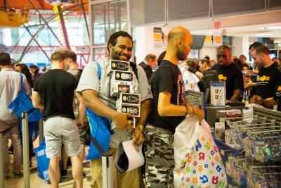 An attendee, center, holds boxes of the BB-8 toy from the Walt Disney Co. Star Wars movie franchise during a 'Force Friday' event at a Toys R Us.