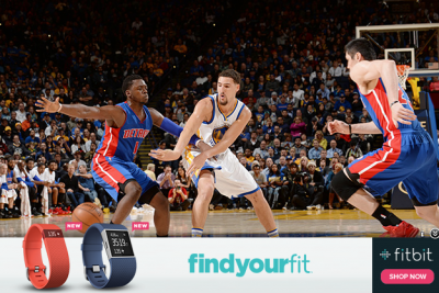 A Fitbit advertisement is overlaid on an image on Sports Illustrated's website.