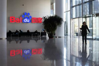 A woman walks past the Baidu logo at the company's headquarters in Beijing, China.
