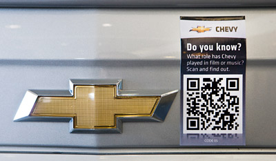 Chevrolet has affixed QR codes on the hoods of cars that, when photographed with a camera phone, will launch microsites with features info.