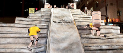 Competitors attempt to climb a 'Mayan' pyramid while tequila casks are hurled at them at a dry run of the 'Cuervo Games' in Orlando on March 6.
