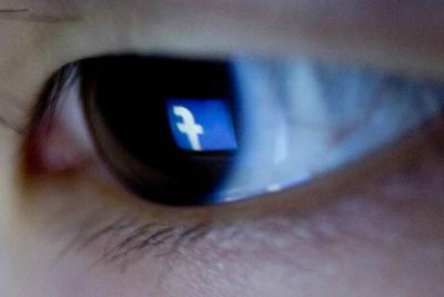 The Facebook logo is reflected in the eye of a woman in this arranged photograph.