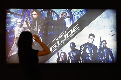 A woman stands near a poster for 'G.I. Joe' at a theater in Beijing, China.