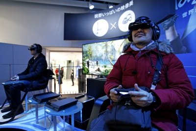 Visitors play video games on Sony Corp's PlayStation 4 at the Sony showroom in Tokyo.