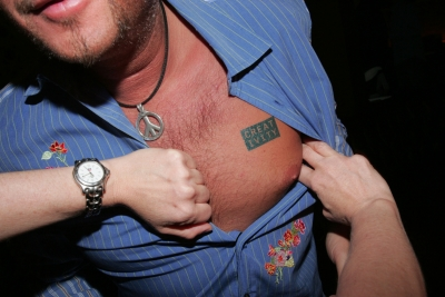 A partygoer gets tattooed with our new logo.