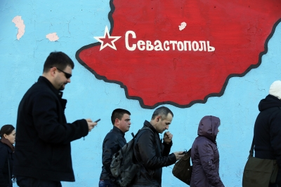 Pedestrians pass a wall mural in Moscow depicting Crimea filled with the flag of the Russian Federation.