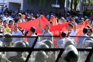Demonstrators hold banners as they protest outside the Japanese Embassy in Beijing, China, on Tuesday, Sept. 18, 2012.