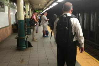 Professional man sporting a backpack on subway.