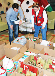 AbelsonTaylor's Matt Schildmeyer and Marie Mikulskis sort gifts for children who wrote letters to the U.S. Postal Service's Letters to Santa program.