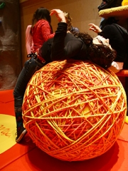 One student stretches like a cat on the giant ball of yarn.