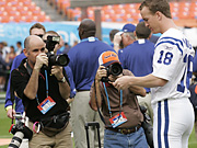 Unless the NFL relents, photojournalists such as the ones above snapping away at Peyton Manning will have to wear vests with the logos of league sponsors Canon and Reebok.