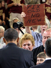 A woman holds a sign as President Barack Obama speaks at a town hall meeting about health care reform in Portsmouth, N.H.