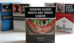 Foreground image shows proposed cigarette packaging in Australia.
