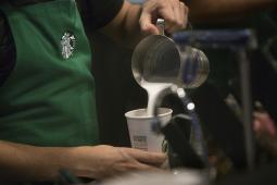 A barista pours frothed milk into a drink inside a Starbucks Corp. coffee shop in New York, U.S., on Monday, Jan. 18, 2016.