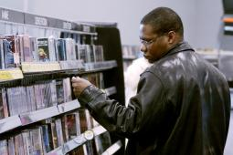 A shopper browses DVDs at a Best Buy.