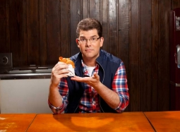 Jon Hein, host of Fast Food Mania, sits at a table with a chicken sandwich at the Harland Sanders Museum and Cafe in Corbin, KY.