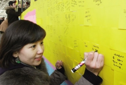 Train passengers at Seoul station write down New Year's wishes on Post-it notes attached to a train.