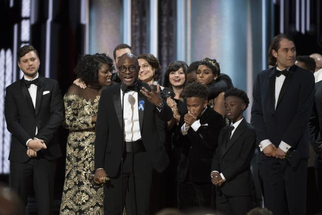 Director Barry Jenkins, surrounded by the cast and crew of 'Moonlight,' accepts the Oscar for Best Picture at the 89th annual Academy Awards.