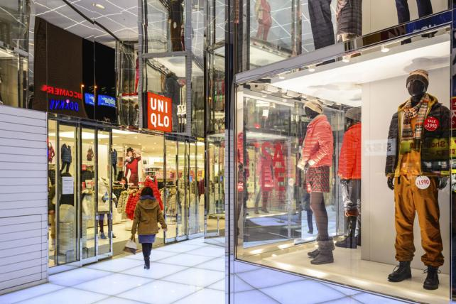 A shopper walks into a UNIQLO clothing store.
