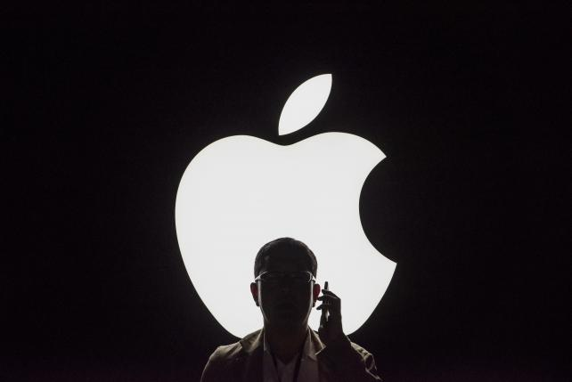 The silhouette of an attendee using an iPhone after the latest product announcements in San Francisco last Wednesday.