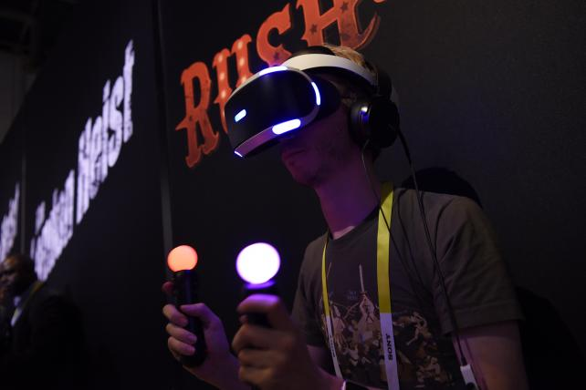 An attendee demonstrates the Sony PlayStation virtual reality gaming headset during the 2016 Consumer Electronics Show in Las Vegas.