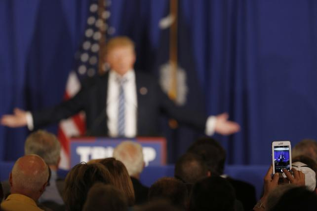 Put down that iPhone! Donald Trump is photographed during a campaign rally at the Turtle Point Clubhouse in Kiawah Island, S.C., on Thursday.