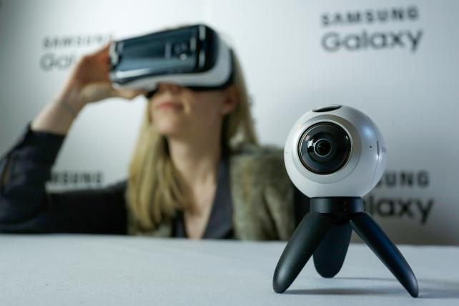 An employee demonstrates the previously released Samsung Gear VR, left, in combination with the new Samsung Electronics Co. Gear 360, a 360-degree video camera, in this arranged photo in London, U.K., on Thursday, Feb. 18, 2016. Samsung showed off new Gal