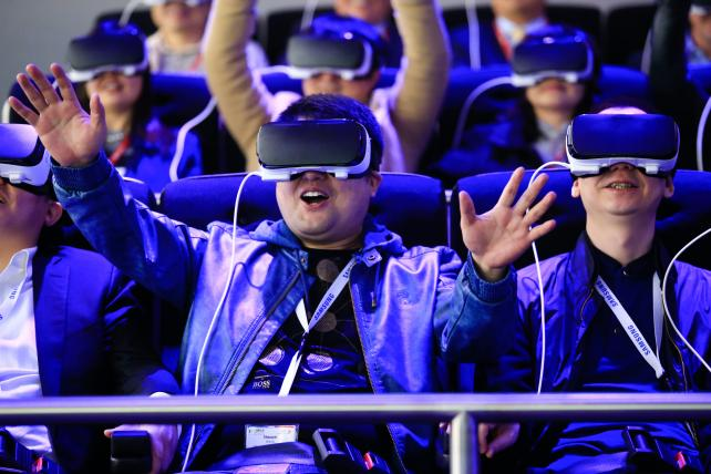 Attendees at the Mobile World Congress in Barcelona try a roller coaster ride using Samsung Gear VR headsets last month.