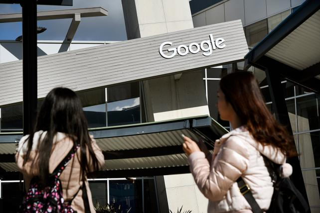 People take pictures of a Google office building in Mountain View, California.