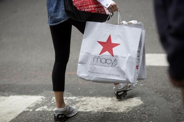 A pedestrian carries a Macy's shopping bag.