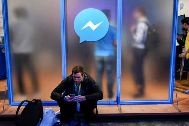 An attendee sits in front of a messenger logo during a Facebook developers conference in San Francisco.