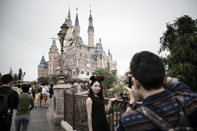 A visitor wearing Minnie Mouse ears poses for photographs at the Shanghai Disneyland theme park.