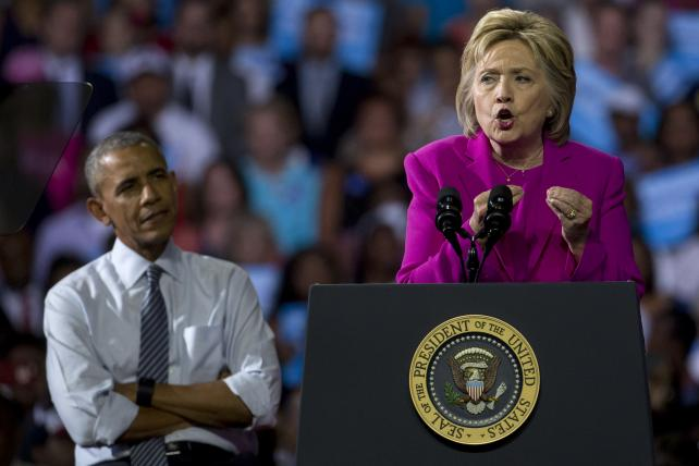 Hillary Clinton as President Obama listens during a campaign rally in Charlotte, N.C., on Tuesday. Obama made his debut campaign appearance on Clinton's behalf hours after the FBI director called Clinton's handling of sensitive e-mails as secretary of sta