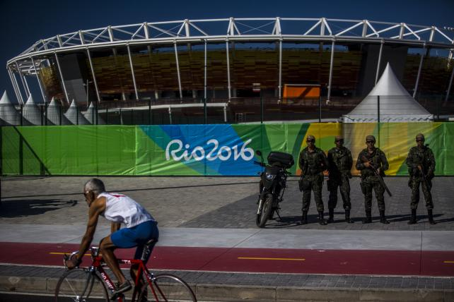 A cyclist rides past military soldiers who are standing guard in front of Olympic Park in the Barra da Tijuca neighborhood ahead of the 2016 Olympic Games in Rio de Janeiro, Brazil, on Sunday, July 24, 2016.