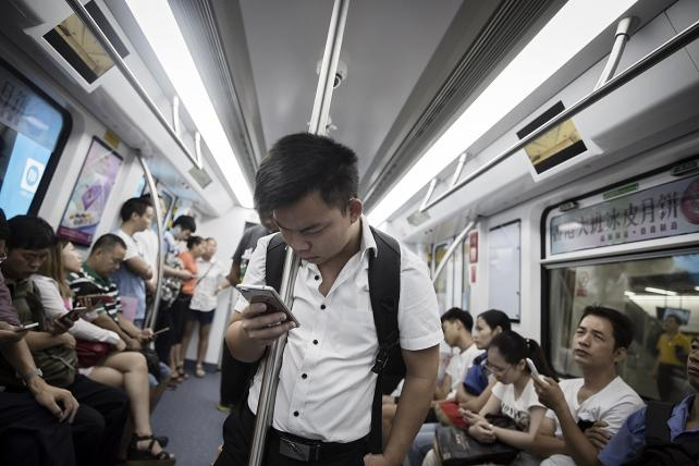 A passenger looks at a smartphone on a subway train in Shenzhen, China, on Tuesday, Aug. 23, 2016.