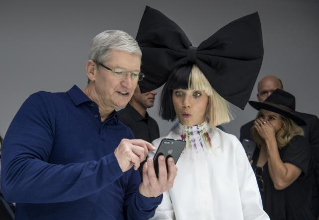 Apple CEO Tim Cook holds an iPhone 7 Plus while speaking with dancer Maddie Ziegler at Wednesday's event introducing the new models.