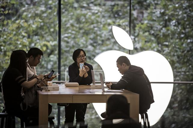Customers look at the Apple Inc. iPhone 7 and iPhone 7 Plus at the Apple Store inside the IAPM shopping mall in Shanghai, China, on Friday, Sept. 16, 2016