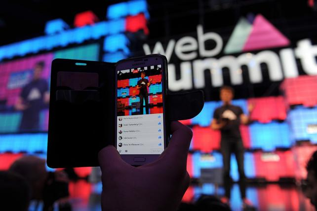 An attendee uses his mobile phone to film a Facebook Live video during the Web Summit in Lisbon, Portugal, on Nov. 7.