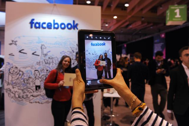An attendee uses a tablet to photograph the Facebook Inc. company pavilion at the Lisbon Web Summit in Portugal on Nov. 8.