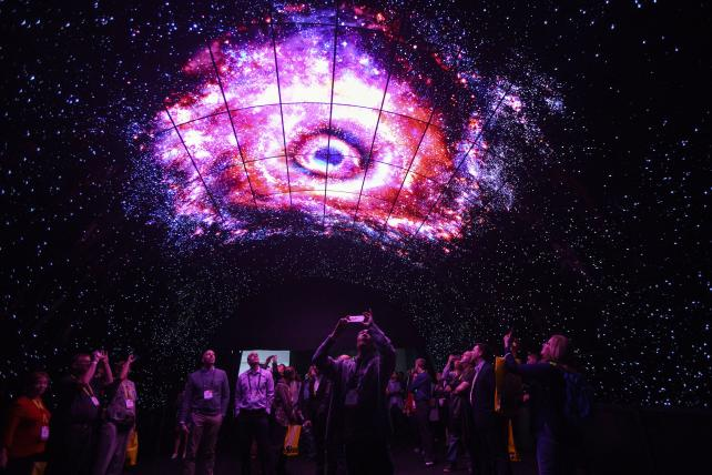 Attendees take photographs while standing under a tunnel wall of LG OLED 4K TVs during the 2017 Consumer Electronics Show, which featured self-driving cars, TVs, drones, robots and a slew of other gadgets.