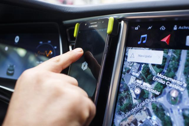 An Uber driver uses the company's smartphone app inside a Tesla Motors Model S.