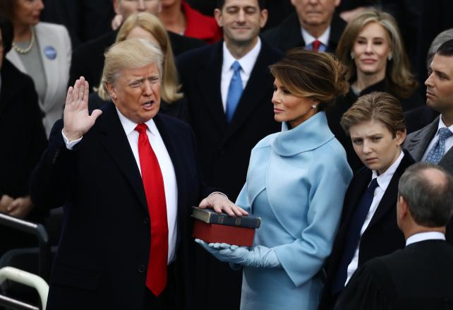Donald Trump takes the oath of office as Melania Trump stands during the 58th presidential inauguration in Washington, D.C., on Friday.