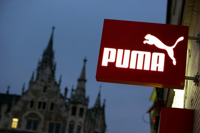A Puma SE logo sits illuminated on a sign outside a sportswear store in Munich, Germany.