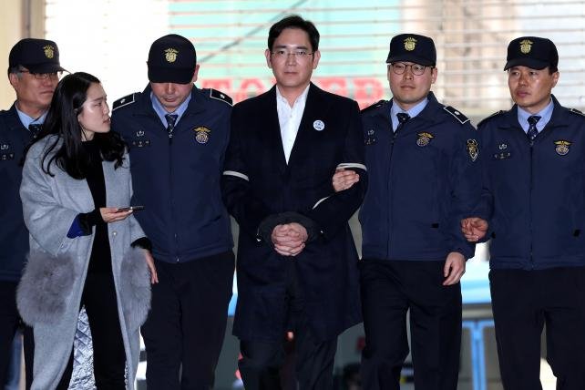 Jay Y. Lee, co-vice chairman of Samsung Electronics Co., center, is escorted by police officers on Saturday.