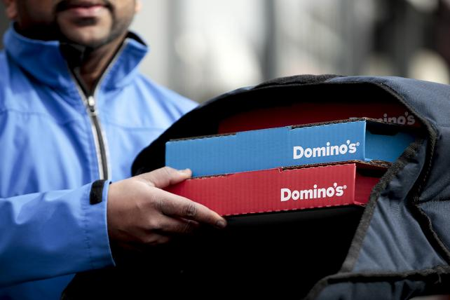 A Domino's Pizza food delivery driver places branded pizza boxes into a thermal container bag outside a Domino's Pizza Group Plc store in London, U.K.