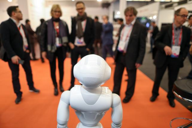 Attendees watch SoftBank Group Corp.'s Pepper humanoid robot on the second day of Mobile World Congress in Barcelona last Tuesday.