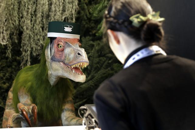 A Kokoro Company robotic dinosaur stands at the reception desk of the Henn na Hotel Maihama Tokyo Bay, operated by H.I.S. Hotel Holdings, as an attendant demonstrates how it works during a media preview in Chiba, Japan, on Wednesday.