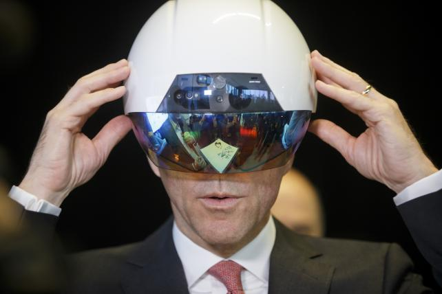 Bill Morneau, Canada's finance minister, tries on a VR helmet during an AI demonstration at the Mars Discovery District in Toronto, Ontario, in March. A new institute for artificial intelligence research opened Thursday with funding from the federal and Ontario governments as well as the private sector.