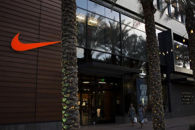 Shoppers pass in front of a Nike store at the Scottsdale Quarter shopping mall in Scottsdale, Arizona,